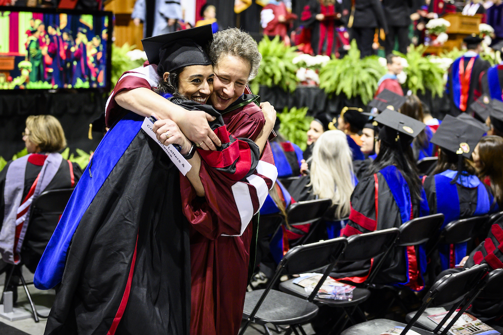 Photo of a new graduate being hugged by a professor.