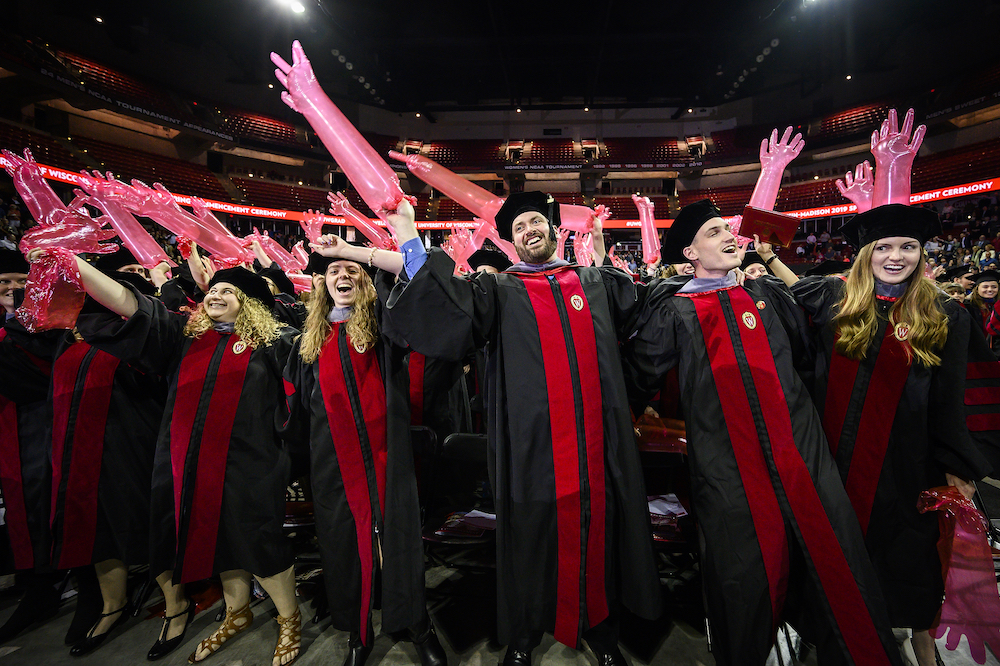 Photo of graduates waving inflated medical gloves.