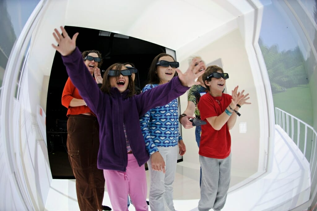 Wearing 3-D eyeglasses and holding a virtual-reality controller, visitors step through a room-sized, computer-generated version of a living room patio door and interact their surroundings during a Living Environments Laboratory Open House at the Wisconsin Institutes for Discovery (WID) at the University of Wisconsin–Madison on Nov. 5, 2011. The room consists of a Cave Automatic Virtual Environment (CAVE), where scientists can re-create a place, observe how someone might use personal-care technology and make related changes earlier in a product's development process. The lab is led by Patricia Flatley Brennan and is part of the publicly funded Wisconsin Institute for Discovery. (Photo by Jeff Miller/UW-Madison)