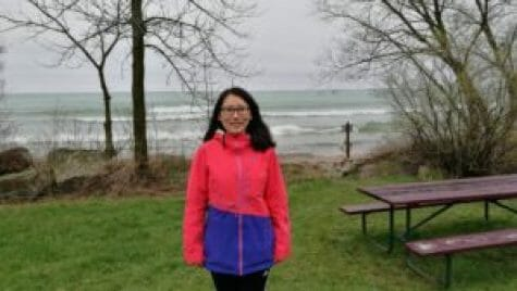 Photo of Yuli Liu standing on the Lake Michigan waterfront