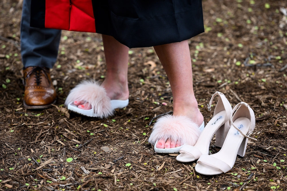 Photo of graduate sporting pink fluffy slides.