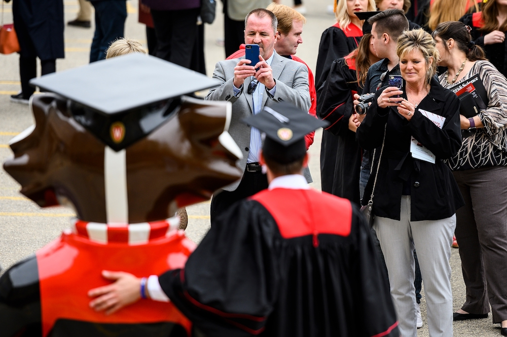 Photo of graduate with his arm around Graduation Bucky