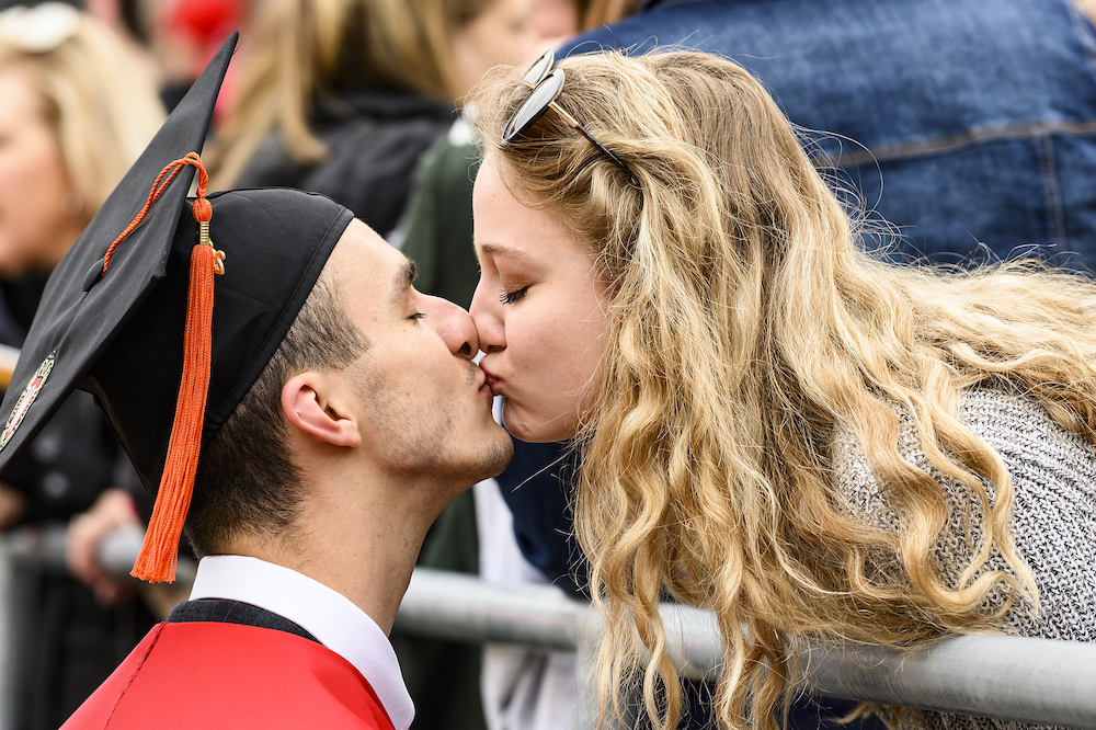 A graduate and his girlfriend share a kiss.