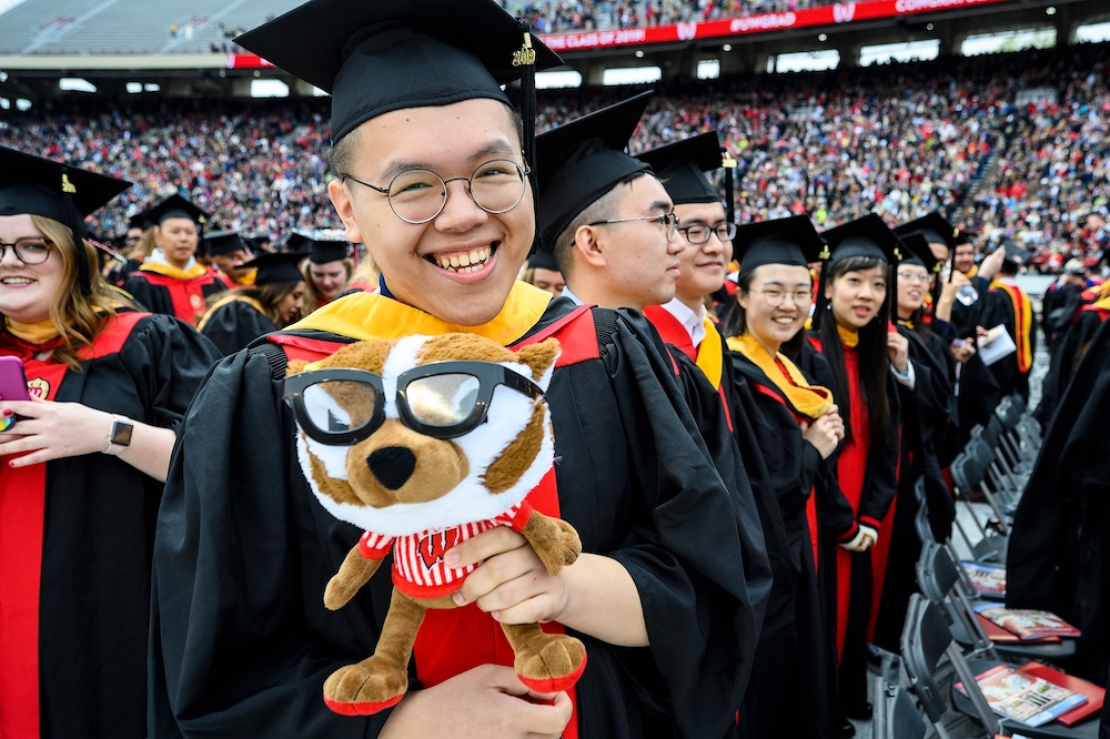 Photo of a graduate holding a plush Bucky Badger