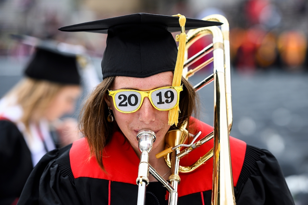 Photo of a graduate playing the trumpet and wearing sunglasses that read '2019.'