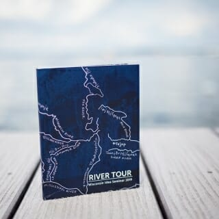 13 May, 2019.  At the beginning of the Wisconsin Idea Seminar each participant receives a copy of the River Tour book, an informative collection of essays, maps, daily itineraries and other components to read and consult during the five-day tour. The cover features an image of handmade indigo-dyed paper crafted by Mary Hark, associate professor of design studies, and overlaid by a hand illustration of Wisconsin's major rivers labeled in Ho-Chunk and English.