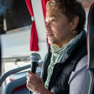 13 May, 2019.  Sheri Johnson, director of UW–Madison's Population Health Institute, delivers a bus talk about community engagement in Milwaukee's Sherman Park neighborhood, one of the destinations of the 2019 Wisconsin Idea Seminar. (Photo by Catherine Reiland/UW-Madison)