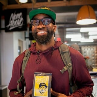 13 May, 2019.  Maanaan Sabir, co-owner of Shindig Coffee at the Sherman Phoenix, holds a bag of coffee that bears his likeness. Sabir shared his perspectives on redefining community wealth in the Sherman Park neighborhood where his coffee shop is located. (Photo by Catherine Reiland/UW-Madison)