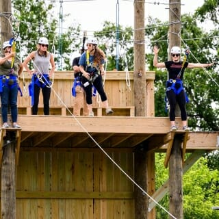 Participants prepare to go on the zip line at the ALPs ropes course during a grand opening of the facility in Stoughton, Wis., on June 21.