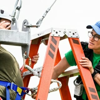 ALPs advisor Mo Kappes, at right, checks the harness and safety lines of a participant preparing to ride the