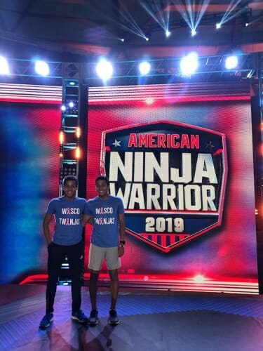 Photo: Green twins standing in front of Ninja show logo