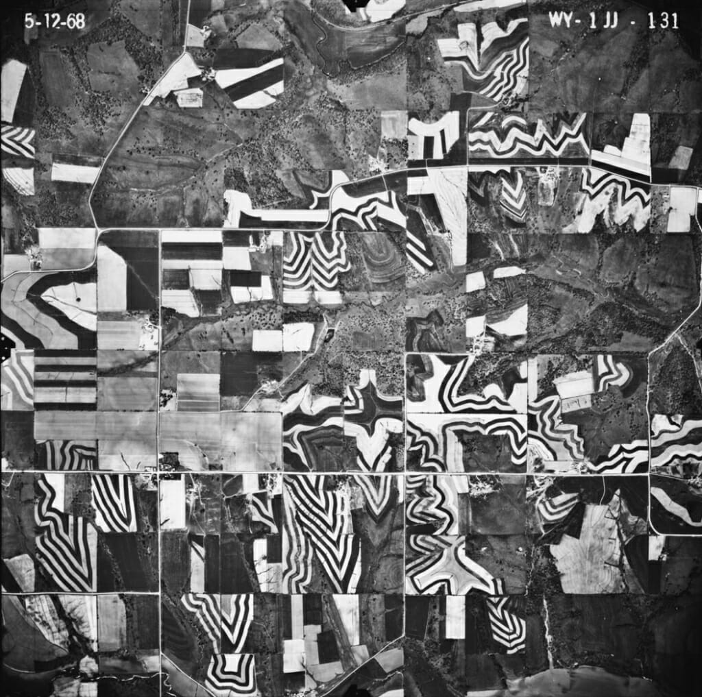 Photo: An aerial photo of farm fields with a distinctive black-and-white striped pattern characteristic of strip cropping.