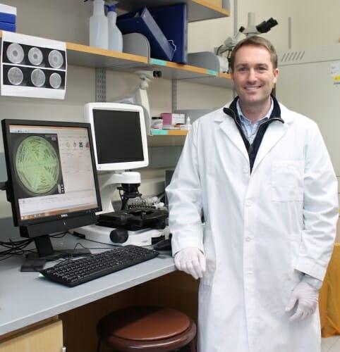 Photo: Warren Rose posing in his lab