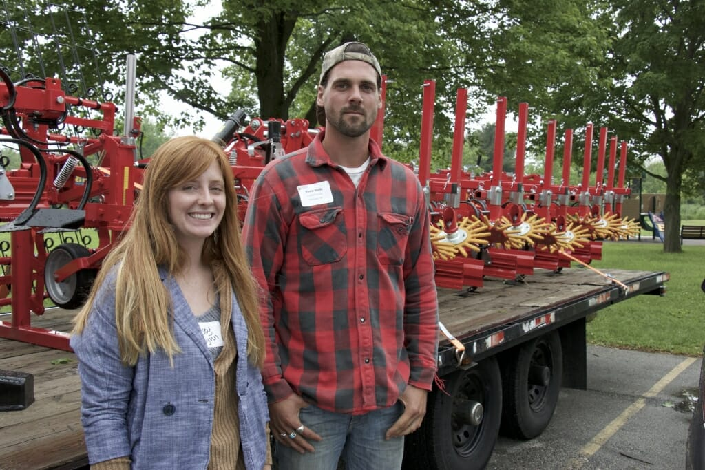A man and a woman stand in front of some farm equipment.