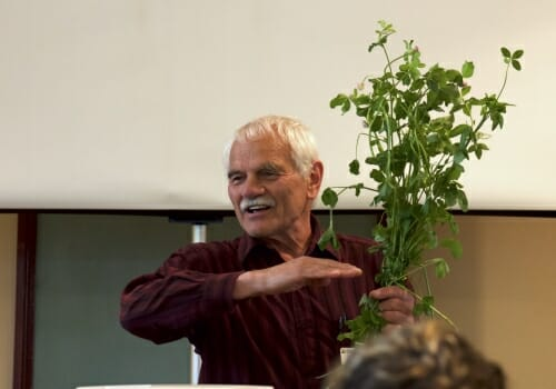 Photo: A man holds a plant and gesticulates as he speaks to a crowd.