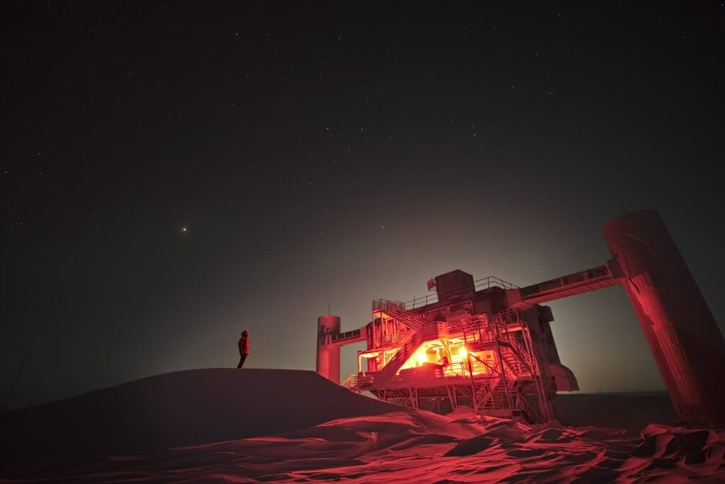 Photo: Reddish-lit exterior of observatory at night backlit by bright moon