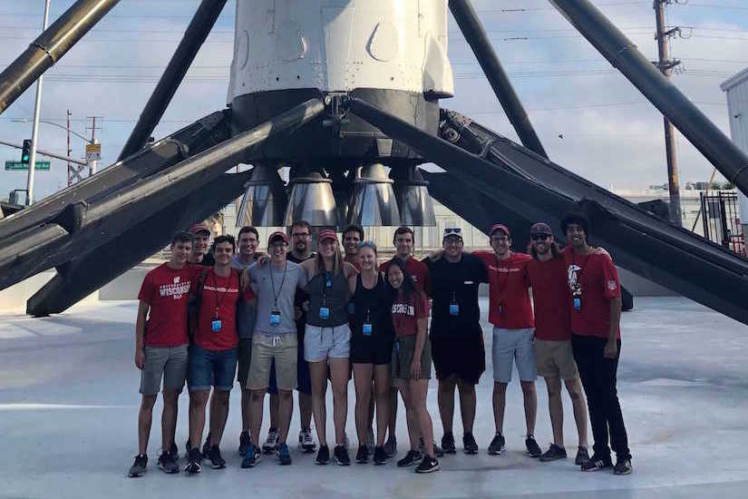 About a dozen students pose for a photo in front of the SpaceX rocket.
