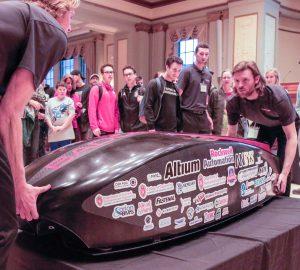 Photo: Students gather around a high-tech vehicle.