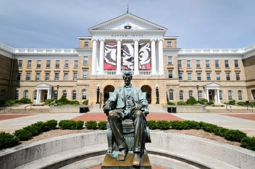 The Abraham Lincoln statue is pictured in front of Bascom Hall at the University of Wisconsin-Madison during spring on June 8, 2016. Hanging between the building's columns is a banner with a graphic of UW-Madison mascot Bucky Badger's face. (Photo by Jeff Miller/UW-Madison)