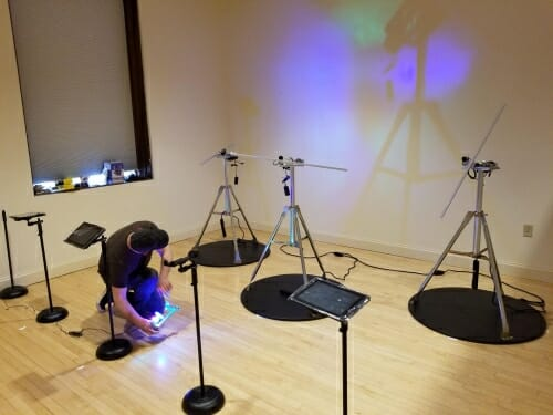 Photo: Hosale crowching amidst tripods and colored lights