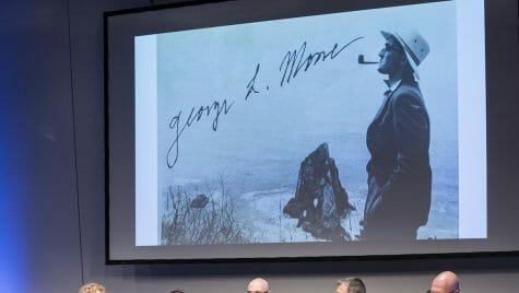 Photo: Panelists sitting beneath projected photo of Mosse