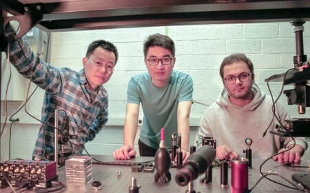 Photo: Three researchers gather in a lab.