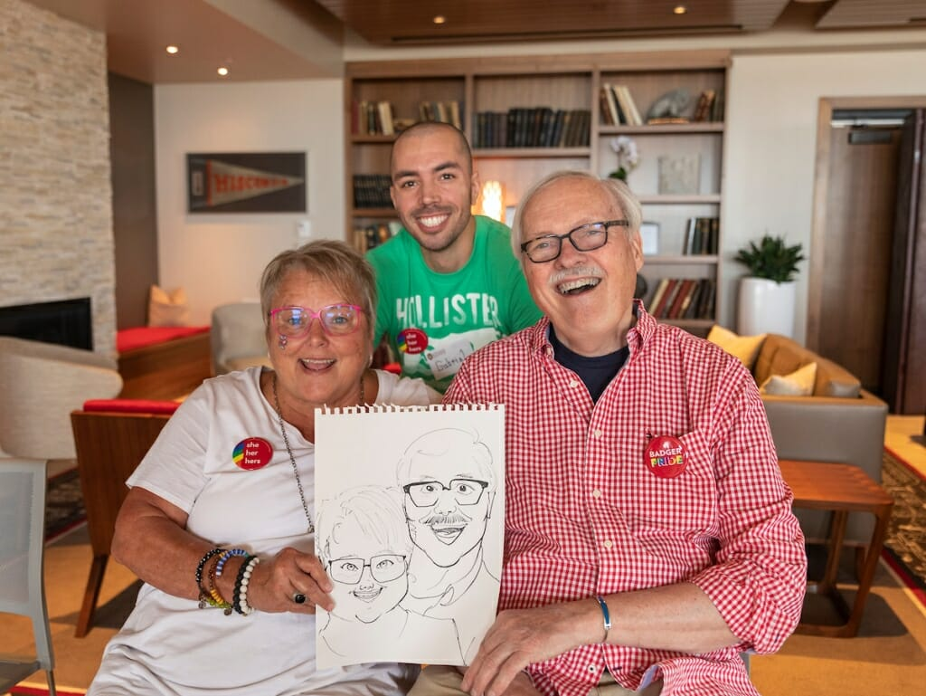Photo: Three people pose and hold a drawing.
