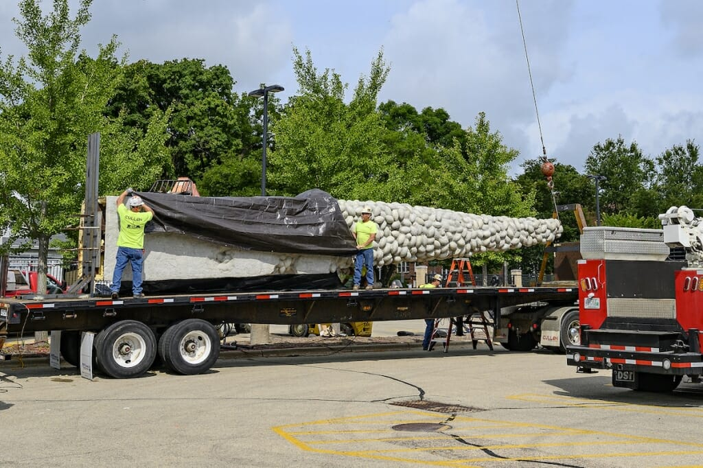 Photo: Workers pull a tarp over a sculpture laying down on a truck.