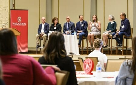 Photo: A panel speaks to a room full of business representatives.