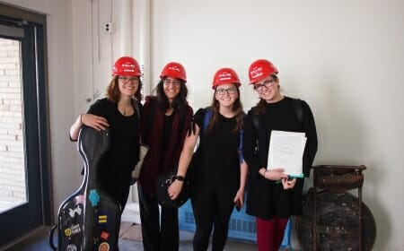 Four women in construction hats pose with their instruments.