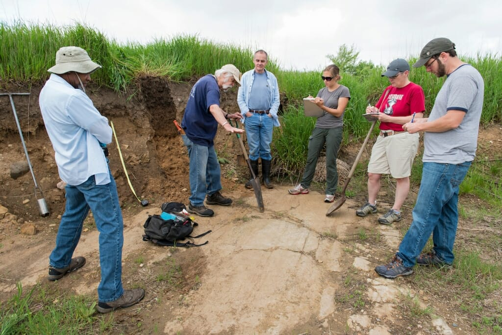 Photo: Fred digging into the ground surrounded by teachers and students