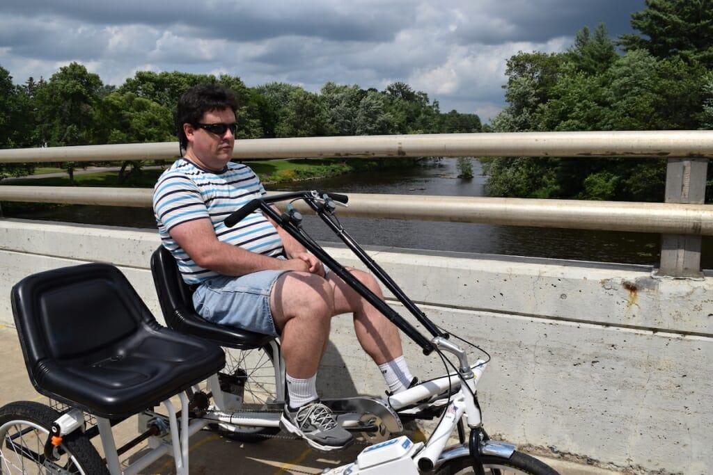 Photo: A man sits on a bike on a bridge.