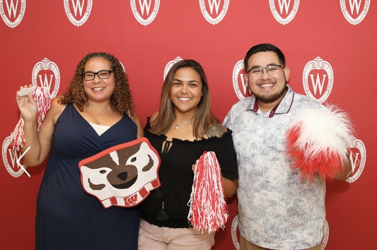 Photo of alumni holding red and white pom poms and a Bucky Badger cutout.