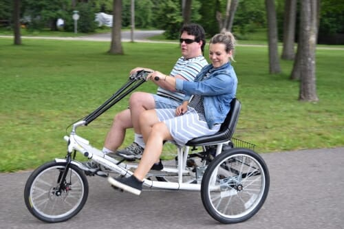 Photo: Two people side by a side on a three-wheel bike.
