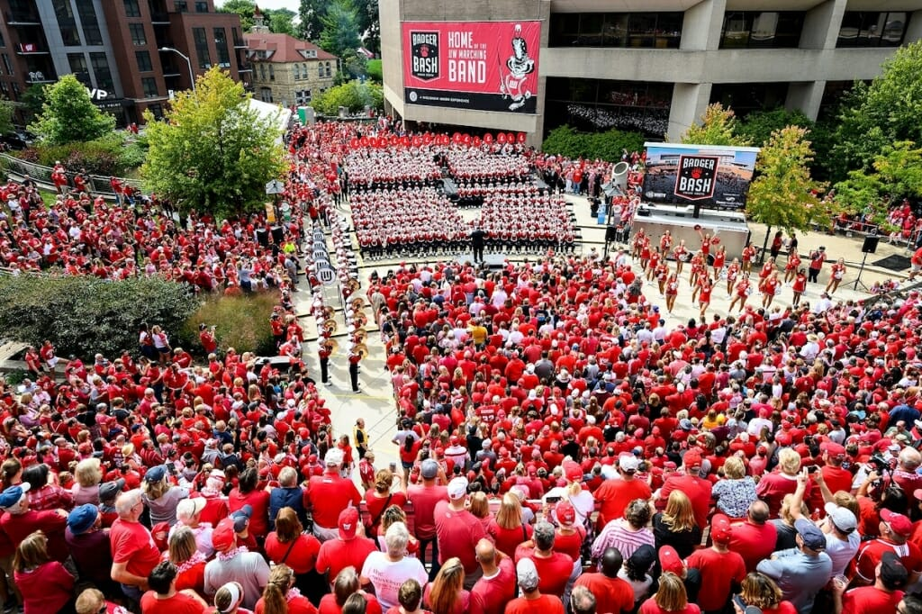 Photo: Wide shot of people, mostly wearing red, listening to band and watching cheerleaders