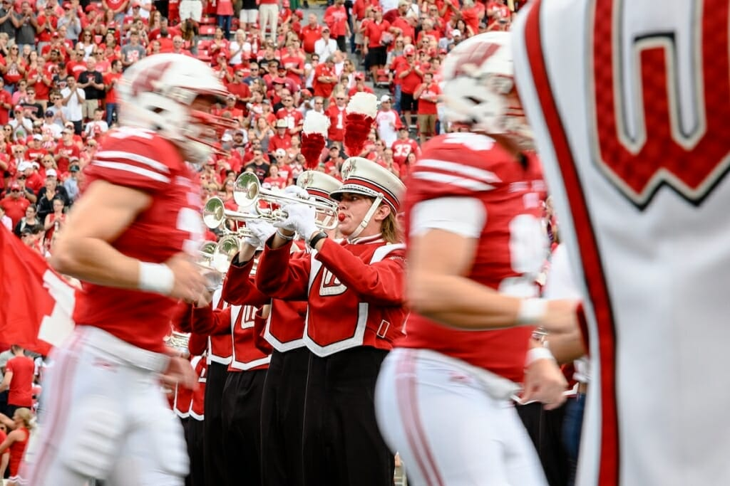 Photo: Uniformed players passing uniformed band members playing horns