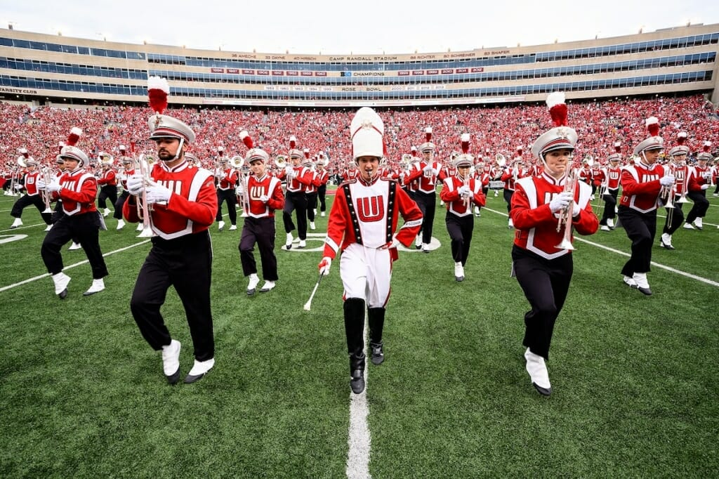Photo: Drum major with baton surrounded by band members marching