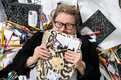 Photo of Lynda Barry holding an illustrated notebook, surrounded by notebooks and colored pens.