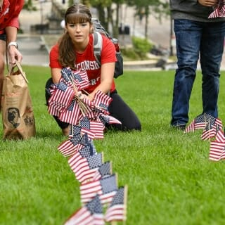 A student carefully lines up the flags being planted.