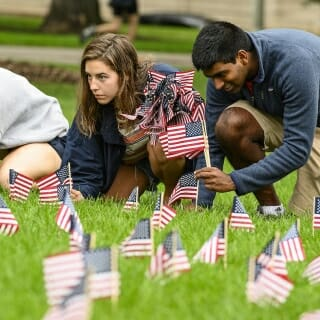 Molly McEneany (left) and Dil Robin line up a row of flags as they place them.