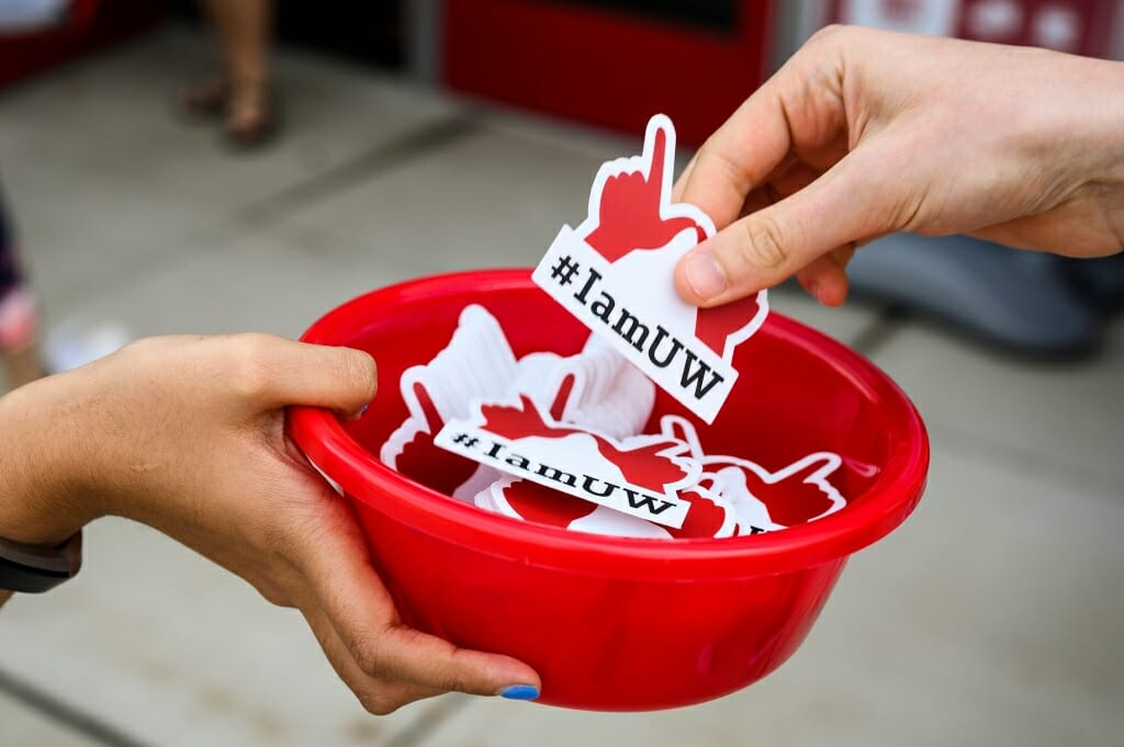 Photo: Closeup of person's hand holding bowl of stickers and another person taking one