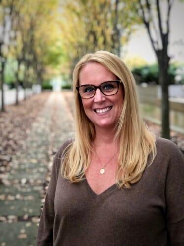 Photo: Outdoor portrait of Emilie Hofacker standing along a tree-lined sidewalk