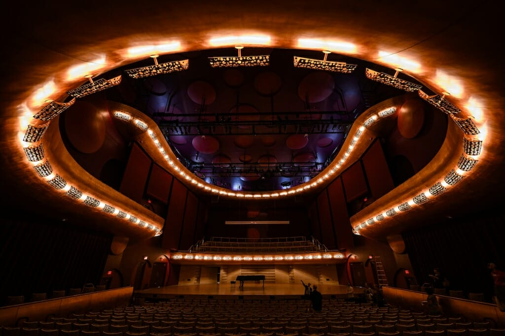 Photo: Inside of dark concert hall with lights on ceiling