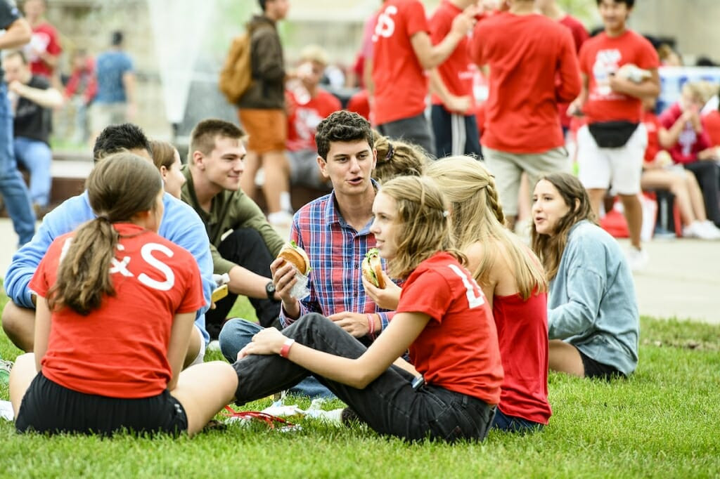 Photo: A group of students sit on the grass and eat.