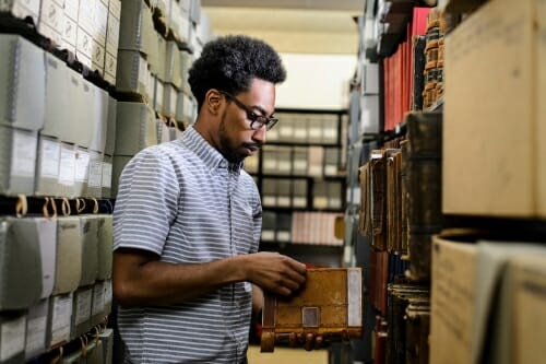 Photo: Long standing between library shelves paging through book