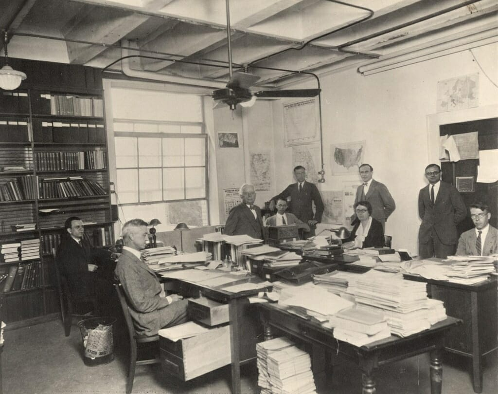 Photo: People sitting and standing in office around desks piled with papers