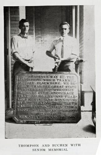 Photo: Students standing behind plaque placed on floor