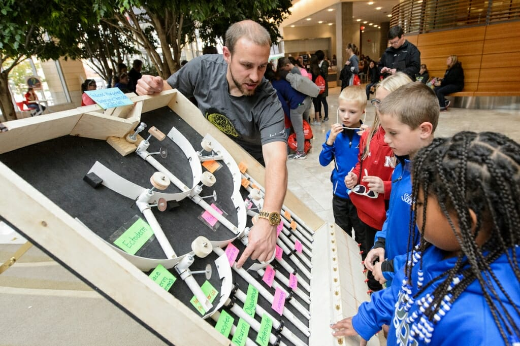 Photo: College student showing children an exhibit