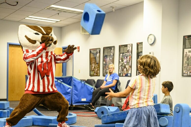 Photo: Bucky Badger plays catch with a young child.