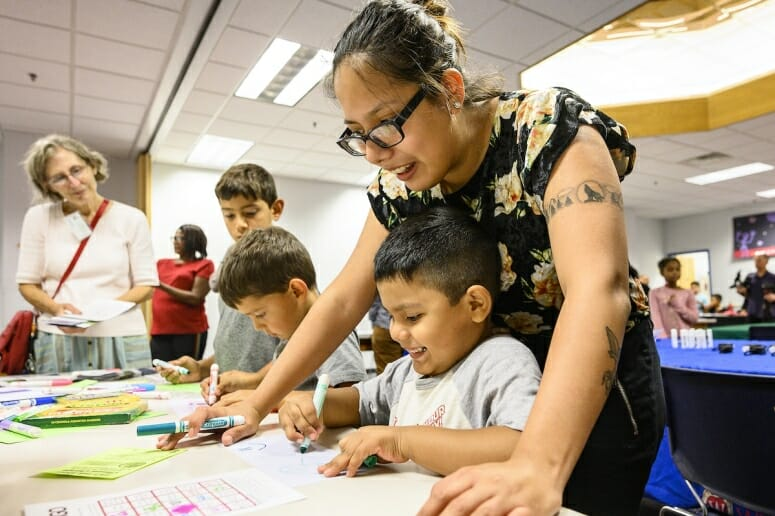 Photo: A boy draws on paper while his mother looks over his shoulder and smiles.
